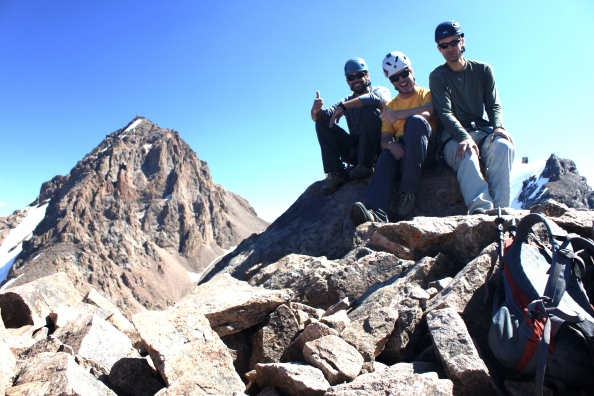 The crew on the summit with the beauty of Komsomol Peak behind