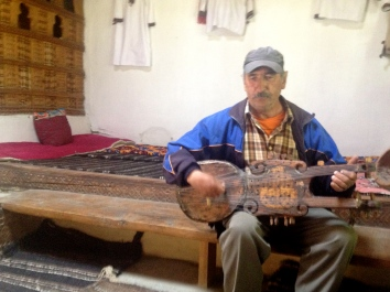 The curator of the Pamiri house museum playing on his Pamiri instrument, which is significantly more elaborate looking than the Kazakh dombra